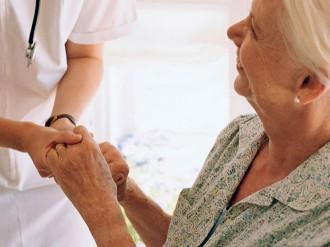 enfermera cogiendo manos de mujer mayor