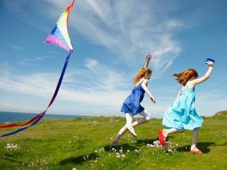 niñas en el campo con cometa