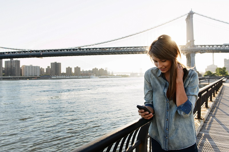 Young woman using cell phone, Manhattan Bridge, Brooklyn, USA